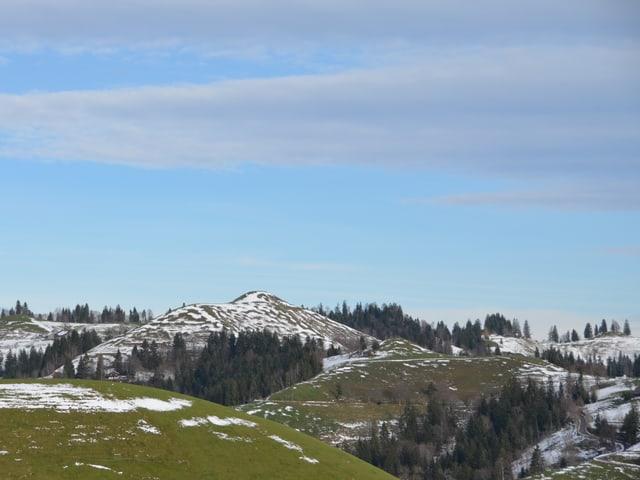 Hügellandschaft mit Schneeflecken auf der Wiese.