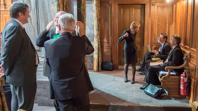Bundesrätin spricht in der Wandelhalle mit ihren Beratern.