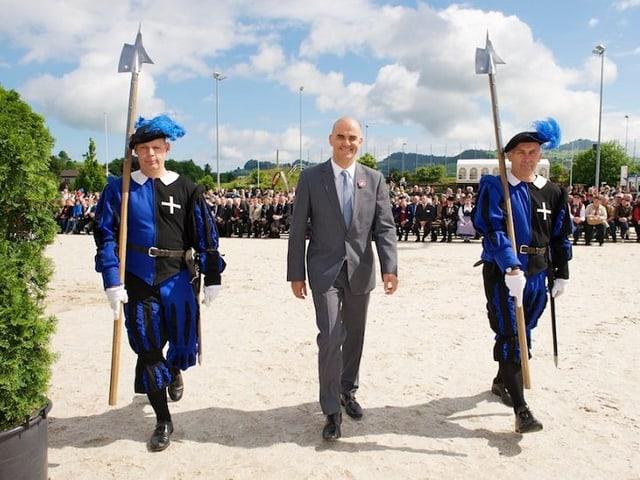 Der Bundesrat steht zwischen zwei Gardesoldaten.