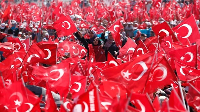 Persunas che fan ir vi e nà bandieras tircas.
