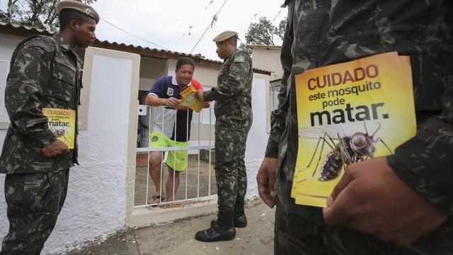 Soldaten mit Flugblättern zum Zika-Virus reden mit einem Bürger