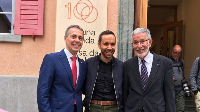Ignazio Cassis, cusseglier federal, Mario Pacchioli, chantadur che fa part dal program e Johannes Flury, president da la Lia Rumantscha.