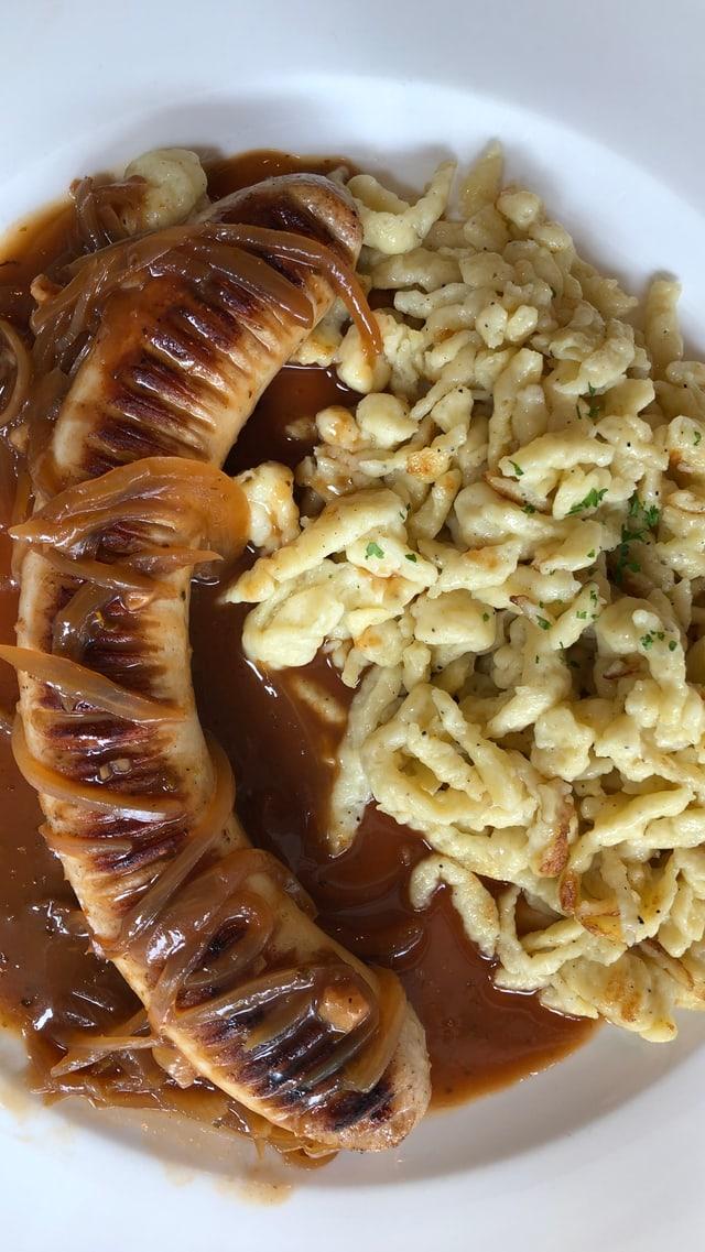 Teller mit Spätzle und Bratwurst.