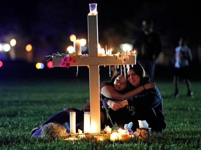 Trauernde Leute vor Kreuz.