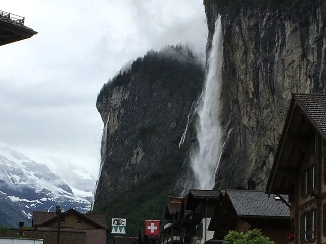Dorf in engem Tal mit Felswänden. Von den Wänden stürzen sich Wasserfälle.