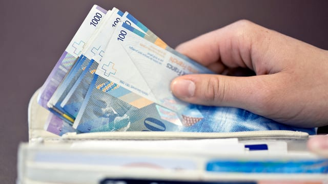 Eine Hand nimmt Hunderter-Noten aus einem Portmonnaie.