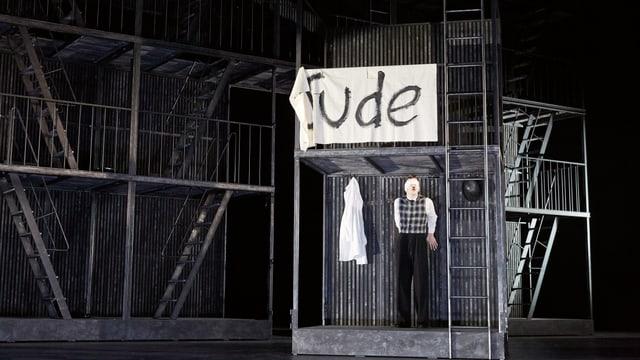 Mann mit weisser Augenbinde steht auf einem Gerüst auf einre Bühne. Über ihm ist ein Stoffbanner mit der Aufschrift «Jude».