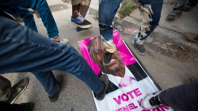 Persunas che passan sin in placat d'elecziun en il Haiti.