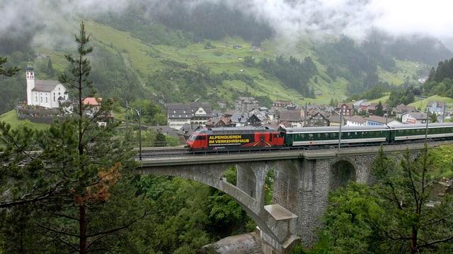 Die SBB Strecke bei Wassen mit einem Zug, der über ein Viadukt fährt.