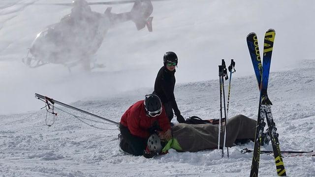 Zwei Personen kümmern sich um einen verletzten Skifahrer, der Rettungshelikopter ist im Anflug.
