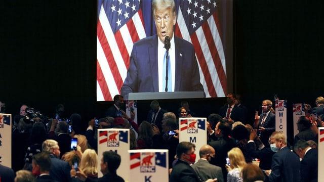 Präsident Trump spricht zur Menge, er ist auf einem Screen zu sehen.