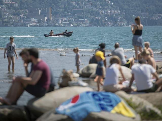 Menschen am See, darauf ein Fischerboot.