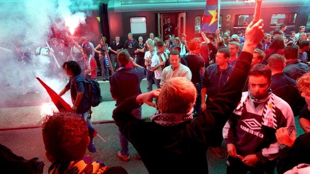 Fans des FC Basels formieren sich zu einer Gruppe und zünden Fackeln an.