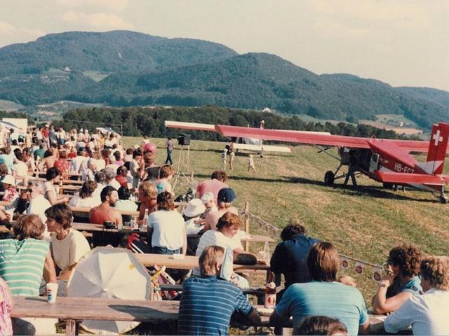 Altes Bild der Flugtage: Menschen sitzen an Festbänken, neben einem Flugzeug.