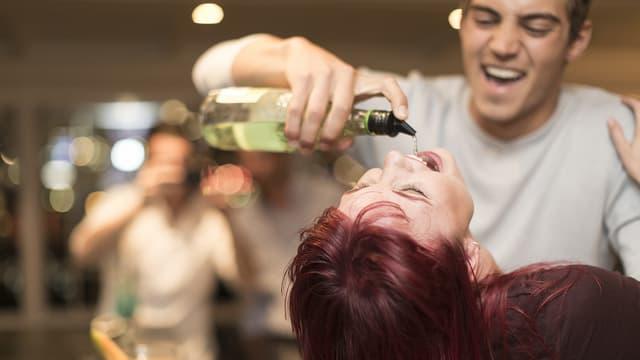 Ein junger Mann leert einer jungen Frau ein Getränk aus direkt aus der Flasche in den Mund.