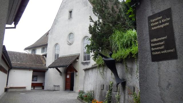 Blick durch das Eingangstor des Klosters. Rechts ein Schild, auf dem die Gäste in verschiedenen Sprachen willkommen geheissen werden.