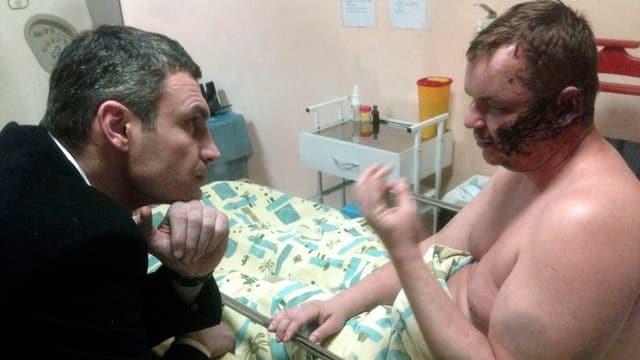 Vitali Klitschko redet am Krankenbett mit dem schwer misshandelten Aktivisten Dmitri Burlatow.