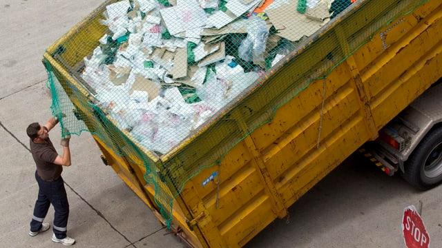 Ein Mitarbeiter von Entsorgung und Recycling Zürich entlädt einen LKW gefüllt mit Abfall.
