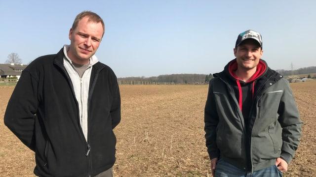 Zwei Männer stehen auf einem Feld