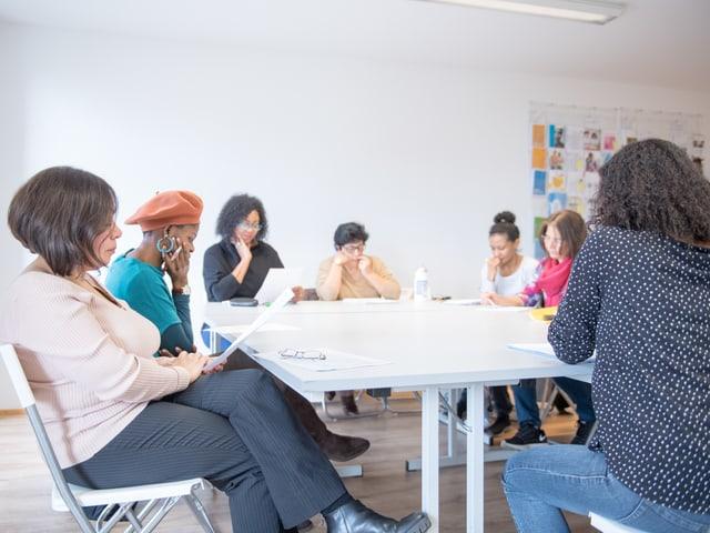 Ligia Vogt sitzt mit mehreren Migrantinnen um einen Tisch.