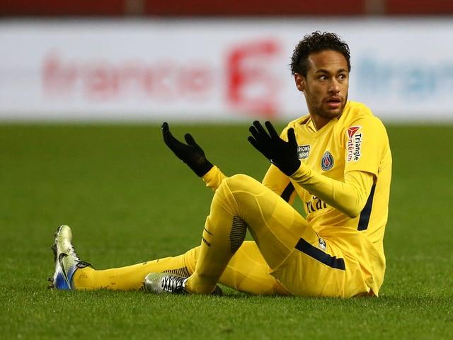 Neymar sitzt auf dem Spielfeld und beklagt sich.