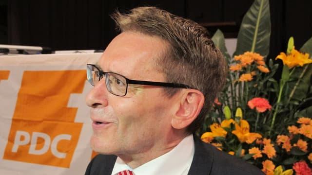 Mann mit Brille, im Hintergrund CVP-Logo und Blumenstrauss