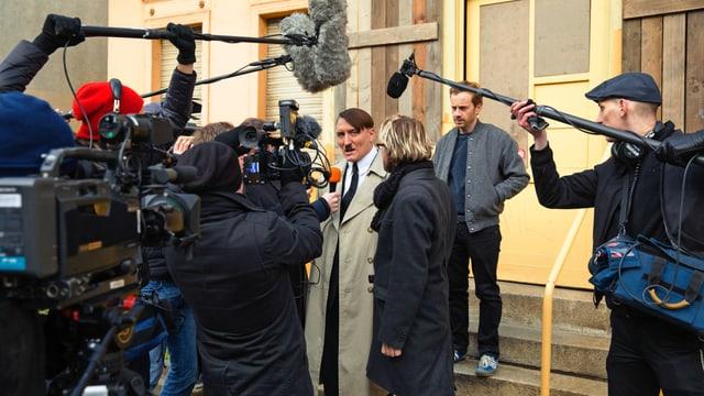 Adolf-Hitler-Darsteller umringt von Journalisten.