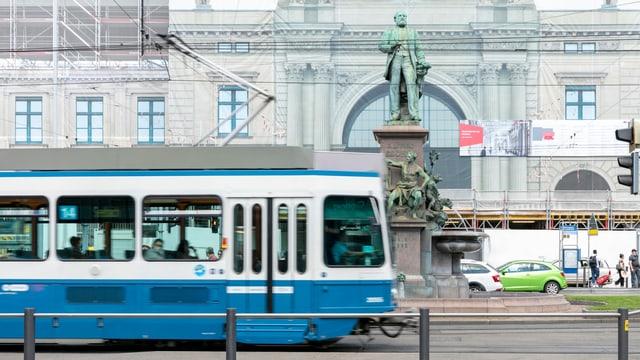 Ein Tram fährt an einer Statue vorbei.