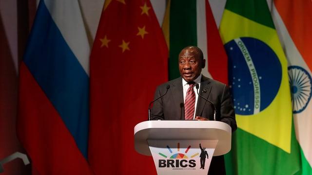 Der südafrikanische Präsident vor den Flaggen der BRICS-Mitgliedsstaaten
