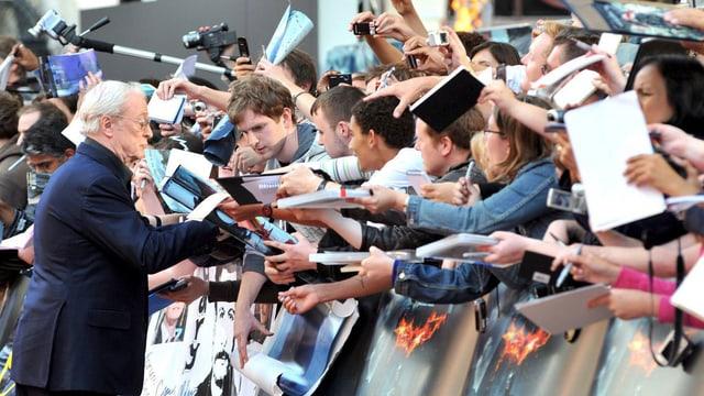 Ein Mann unterschreibt einer Reihe von Fans die Plakate