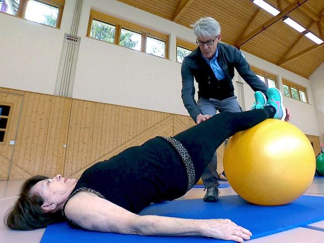 Frau liegt am Boden, die Füsse auf einem Gymnastikball, und streckt ihren Körper durch.