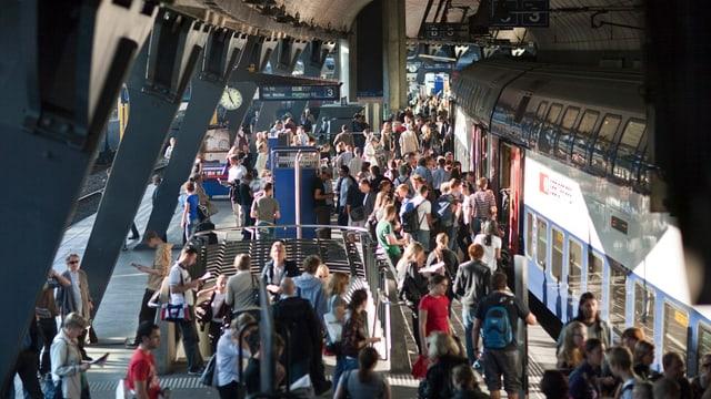Ein Zug hält am Bahnhof Stadelhofen, viele Menschen steigen ein und aus.