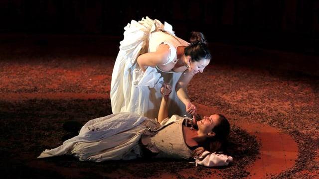 Frau liegt am Boden, eine andere beugt sich darüber, beide in barocken Kostümen.
