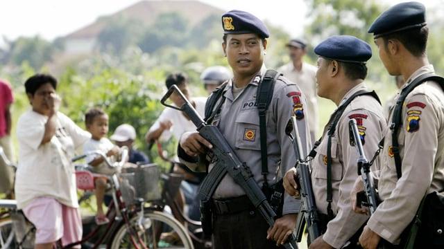 Indonesische Polizisten stehen auf der Strasse