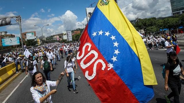 Demonstrantin mit SOS-Flagge in den venezolanischen Farben