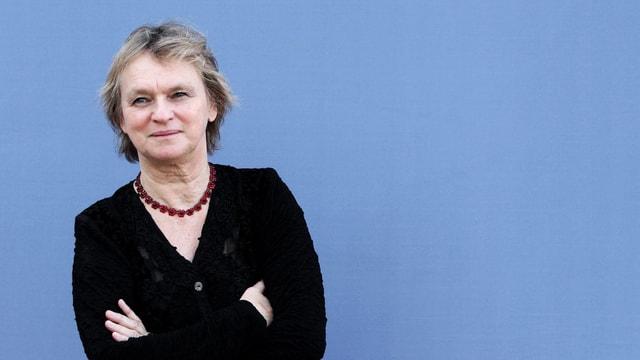 Porträt halbnah von Elke Heidenreich, mit verschränkten Armen, vor blauem Hintergrund.