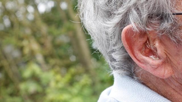 Ohr eines alten Menschen, der ein Hörgerät trägt.