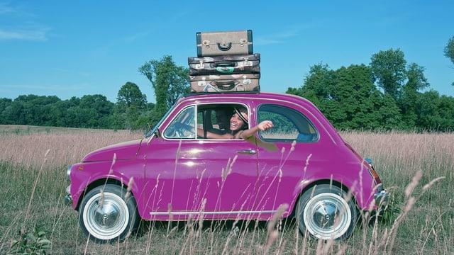 Ein kleines Auto in Pink, auf dem Dach drei Koffer.