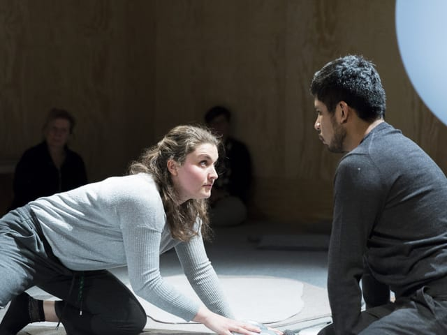 Eine Frau kauert auf dem Boden. Sie schaut einen Mann an.