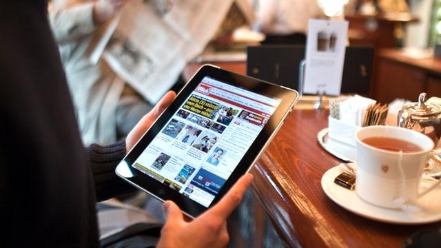 Ein Mann sitzt in einem Kaffee und surft mit dem Tablet