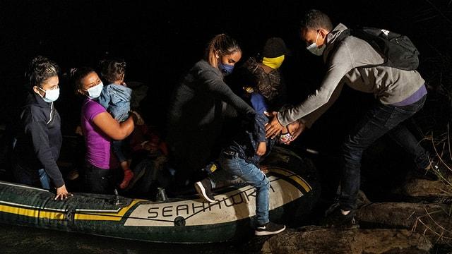 Migrantinnen kommen im Boot an Land in der Nacht