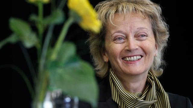 Eveline Widmer-Schlumpf lacht, eine gelbe Blume ist auch mit im Bild.