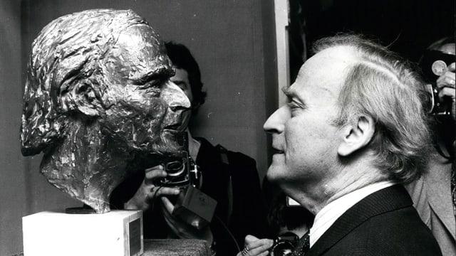 Rechts steht ein älterer Mann und guckt sein Ebenbild als Statue an.