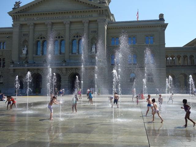 Kinder rennen durch die Wasserfontänen beim Bundeshausplatz