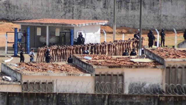 Nackte Insassen stehen in einer Reihe, bewaffnetes Sicherheitspersonal steht daneben