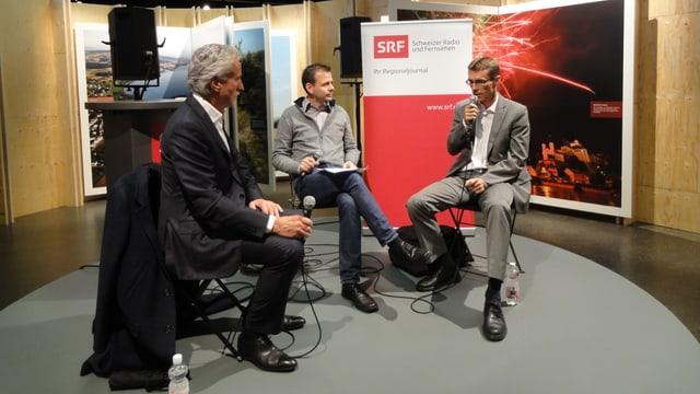 Drei Männer sitzen auf einer Bühne und haben Mikrofone in der Hand.