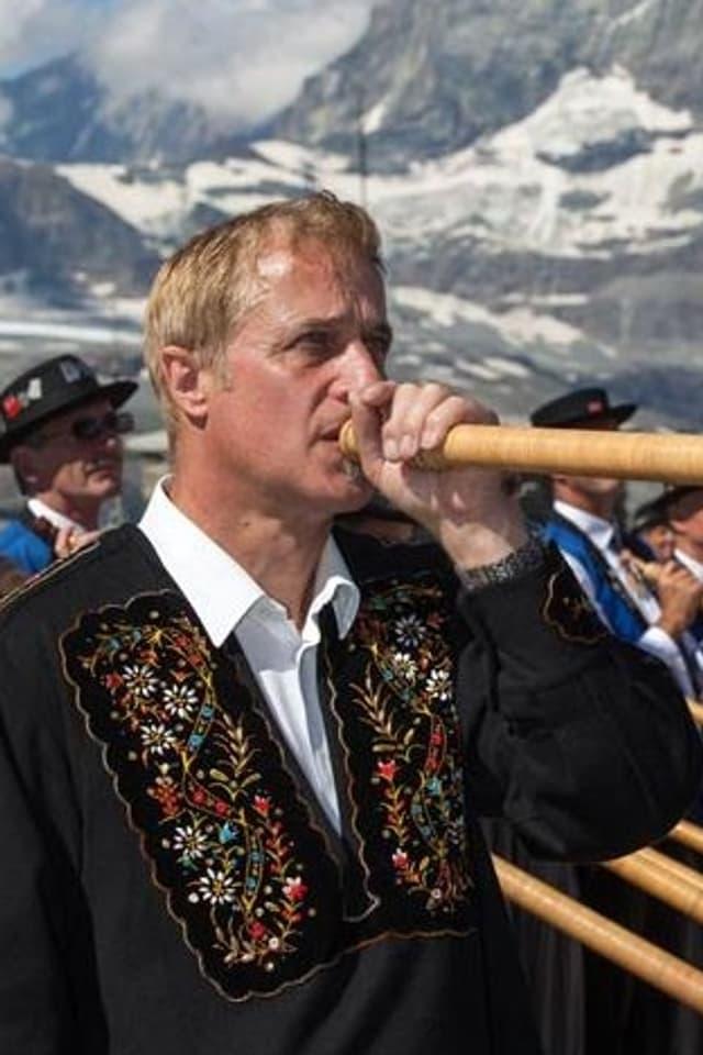 Sigrist in Trachtenhemd bläst andächtig in sein Horn. Im HIntergrund sieht man das Matterhorn.