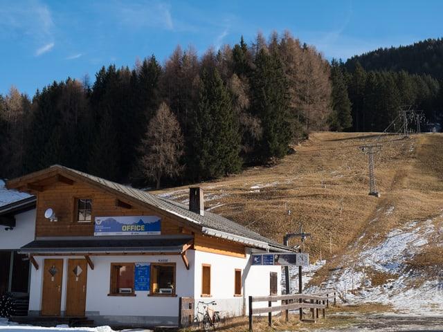 Skilift ohne Schnee, davor Haus
