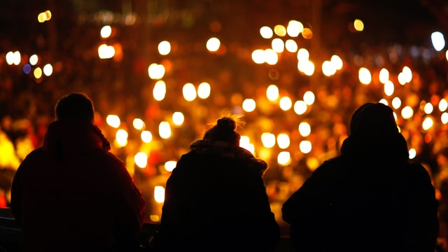 Schwarze Umrisse von drei Menschen, die auf ein Kerzenmeer blicken.