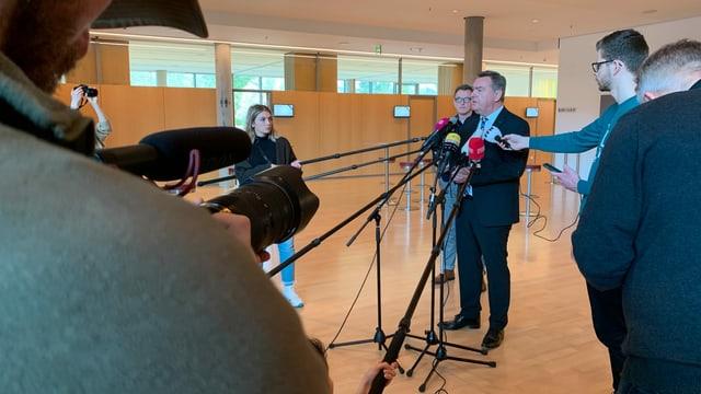 Pressekonferenz, ein Mann spricht vor Mikrophonen